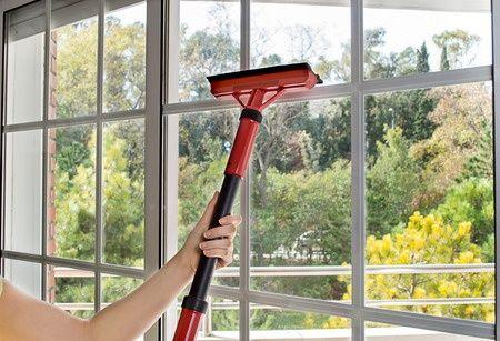 Eine Frau putzt die kunststofffenster