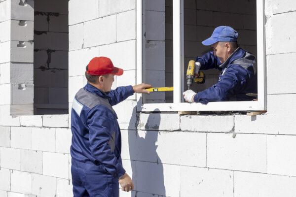 Mitarbeiter installieren polnische Fenster in einem Einfamilienhaus.